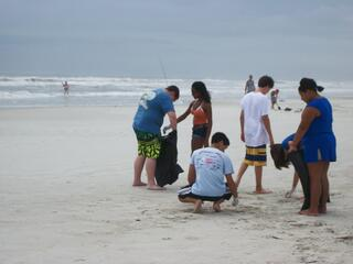 Student volunteering abroad on the beach.